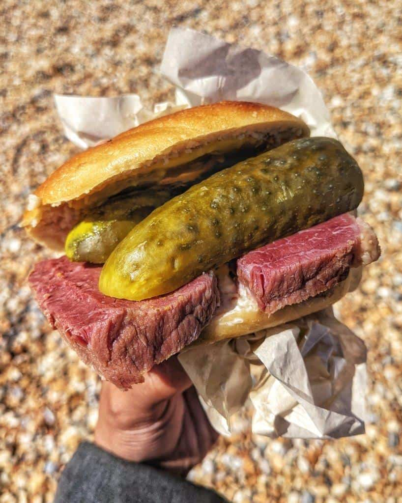 A close up of a hand holding a delicious bagel stuffed with thick slices of salt beef and huge pickled cucumbers, held over a pebbled beach