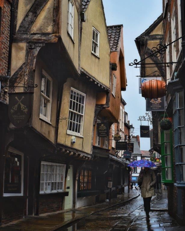 A woman holding a purple umbrella walking down a cobbled medieval looking street in the rain, with overhanging timber-framed buildings