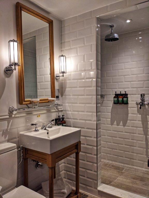 A stylish bathroom tiled white with a large walk-in shower and big mirror above the basin