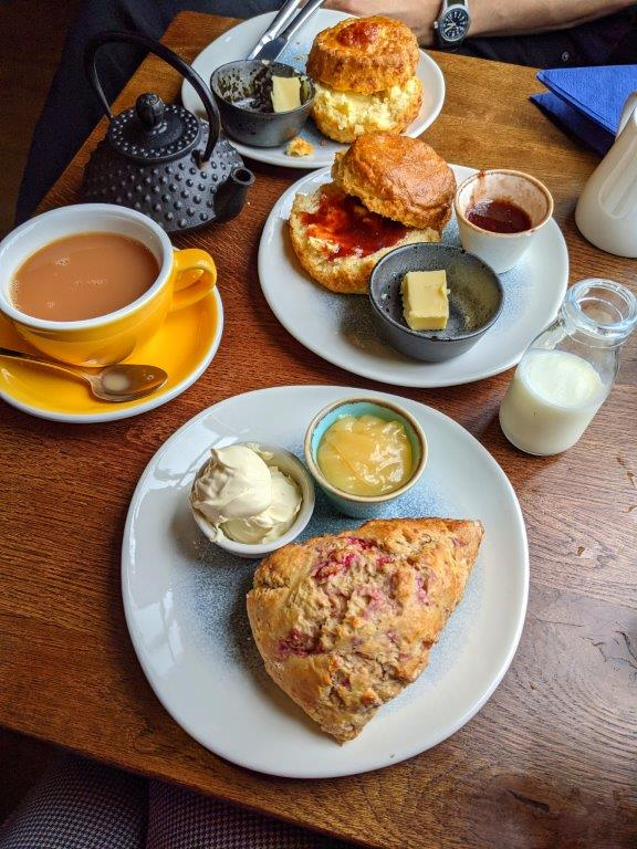 Plates of scones, preserves and clotted cream laid out on a wooden table along with cups and pots of tea
