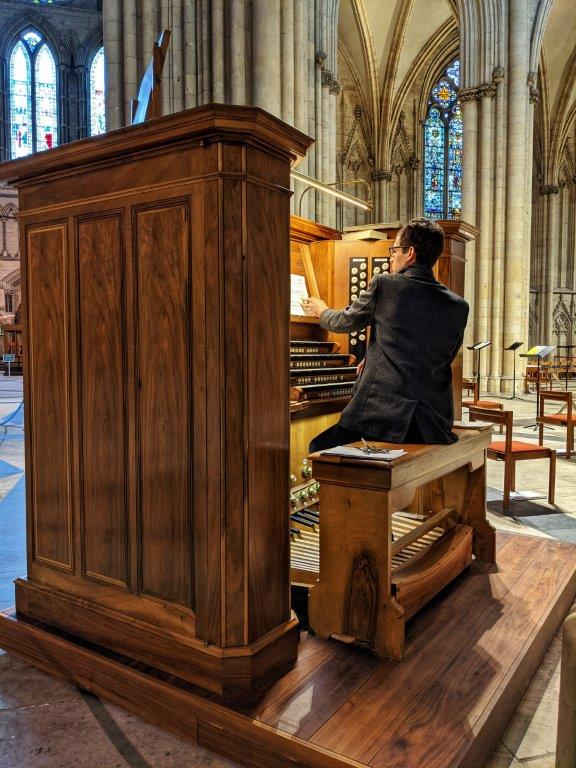 A man sitting on a large piano stool with his back to us, playing the organ in a grand church