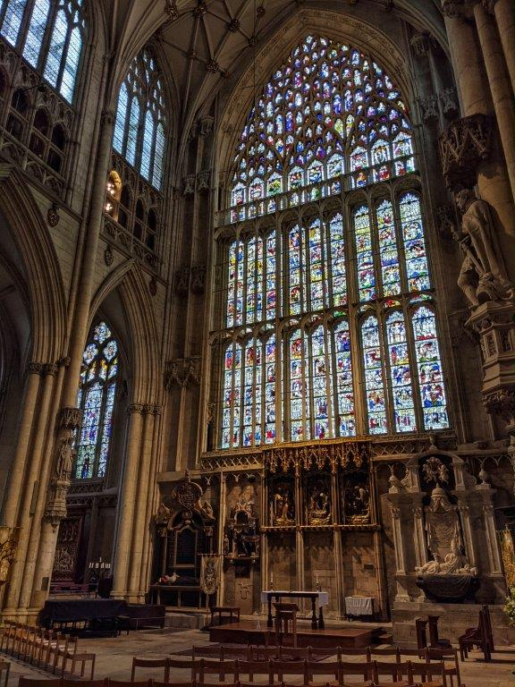 An imposing and intricate stained glass window reaching the full height of the cathedral, about the size of a tennis court. Some chairs in the foreground dwarfed by the great window's presence