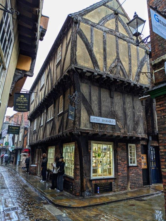 The corner of a medieval building on a cobbled street, with overhanding timber-framed upper stories