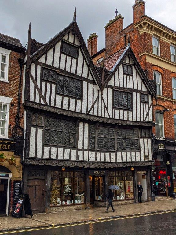 A classic black and white tudor building, the ground floor of which is a shop called 'York Gin'
