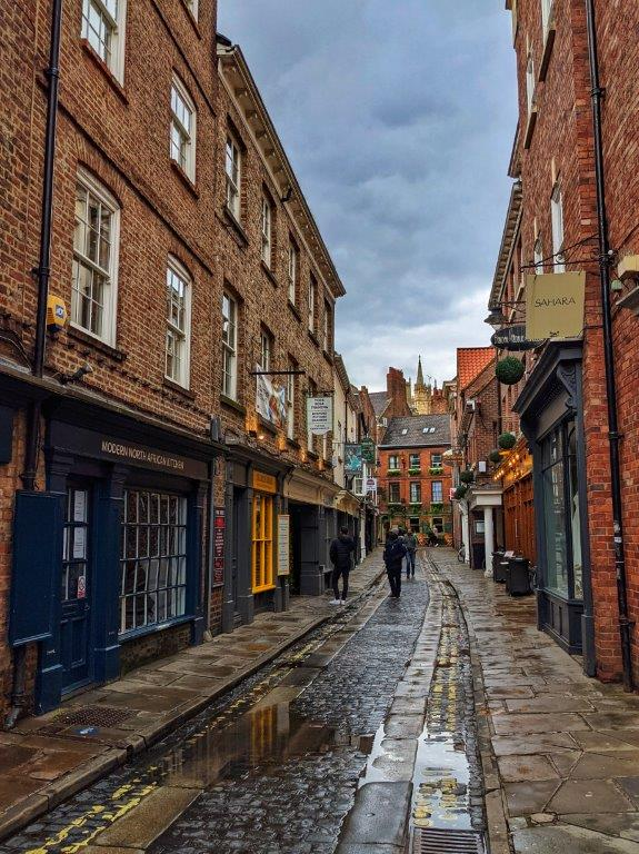The view down a narrow cobbled street after the rain flanked by red brick industrial buildings housing independent shops on the ground floor