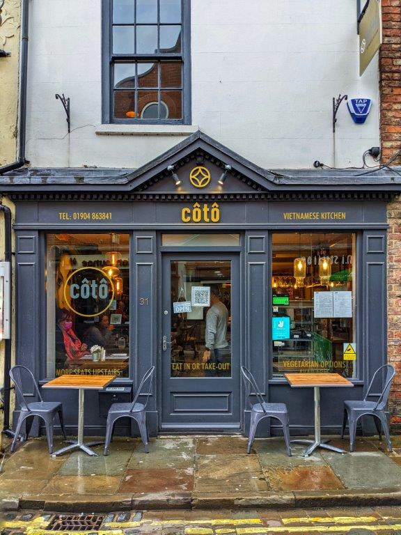 A dark grey shop front with yellow lettering reading 'Coto' and two tables out the front