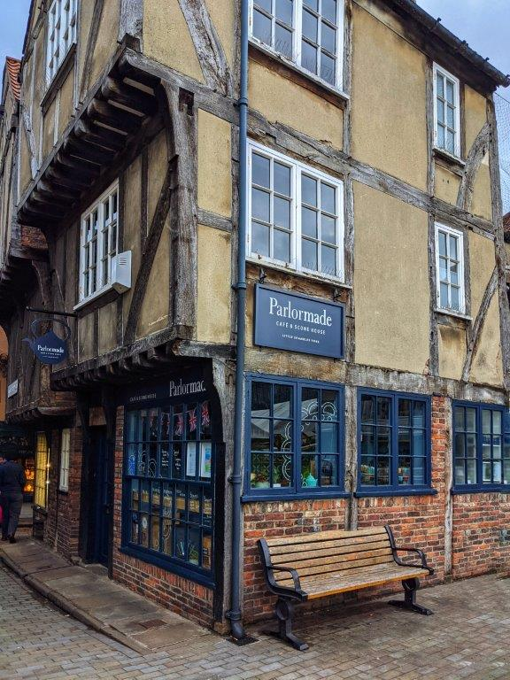 The corner view of a shop called 'Parlormade' in a medieval building with a wooden bench out the front and overhanging timber-framed upper stories