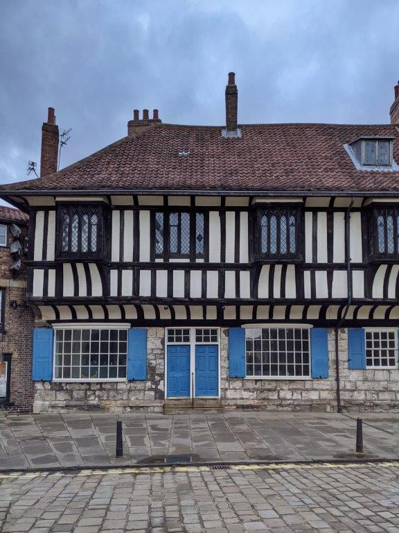 A classic black and white tudor style building with blue doors and window panels