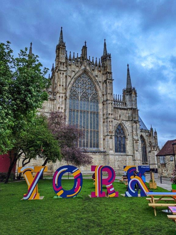 A facade of a cathedral with grass in the foreground on which four large letters read 'YORK'