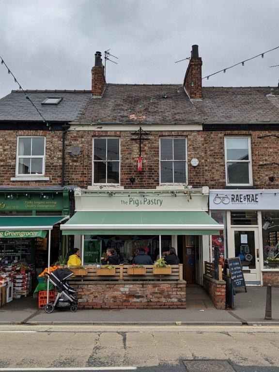 A pale green shop front with an awning, called 'The Pig and Pastry' with a few tables out the front with diners