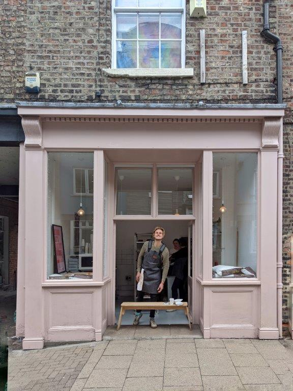 A blush pink shop front with no name, with a man wearing an apron standing in the entrance grinning to camera