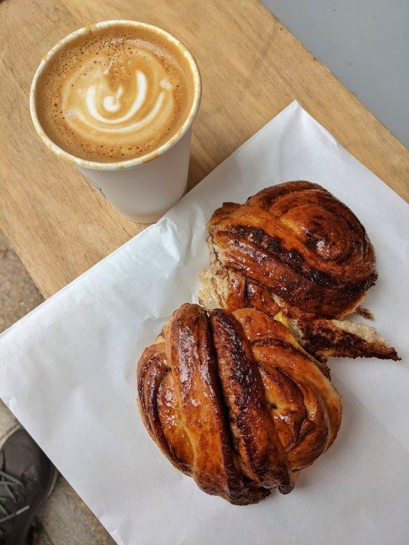 Two glossy buns laid on a paper bag and a coffee in a paper cup on a wooden bench