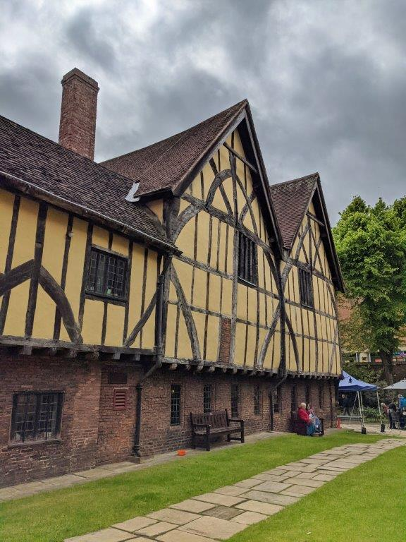 A side view of the exterior of a timber-framed medieval with brick base