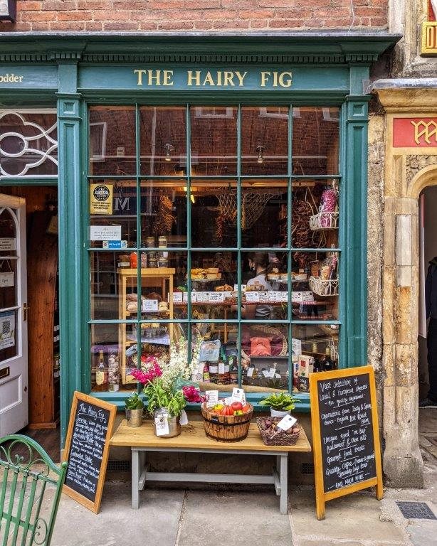 A quaint dark green shop front with lots of glass called 'The Hairy Fig' with the window filled with edible delights