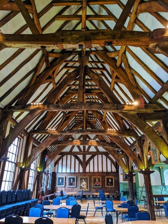 A view of the length of a grand medieval hall with a number of exposed wooden beams in the vaulted ceiling