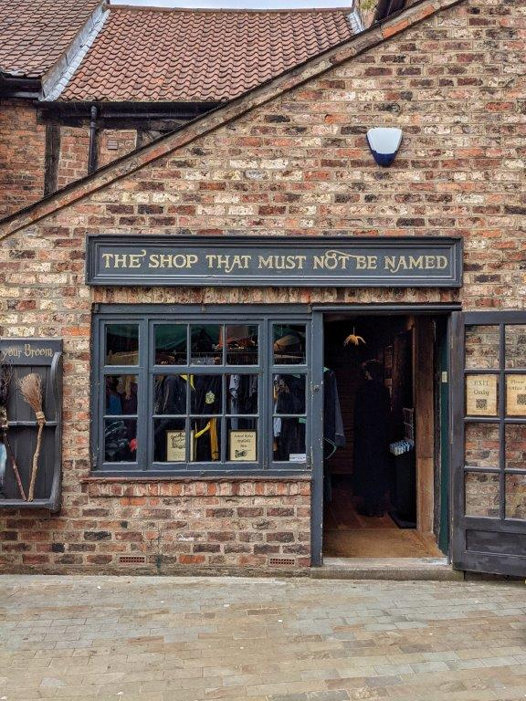 A dark grey and brick shop front called 'The Shop That Must Not Be Named' with the entrance door wide open