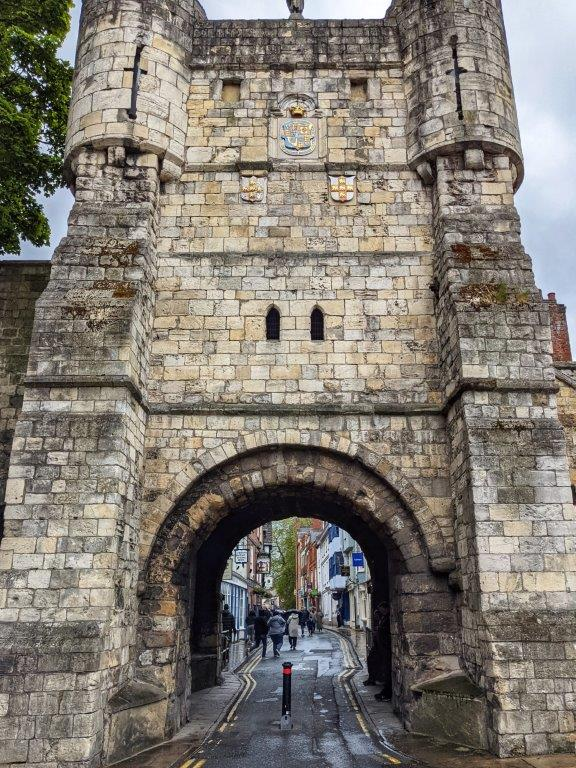 An imposing stone tower with an archway through which pedestrians can walk