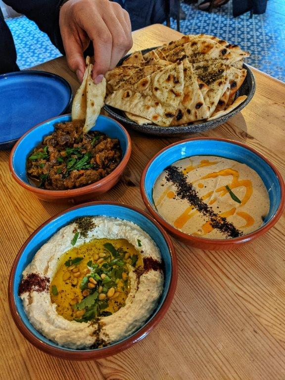 A spread of North African-inspired mezze dishes on colourful crockery, including a big pile of flat breads