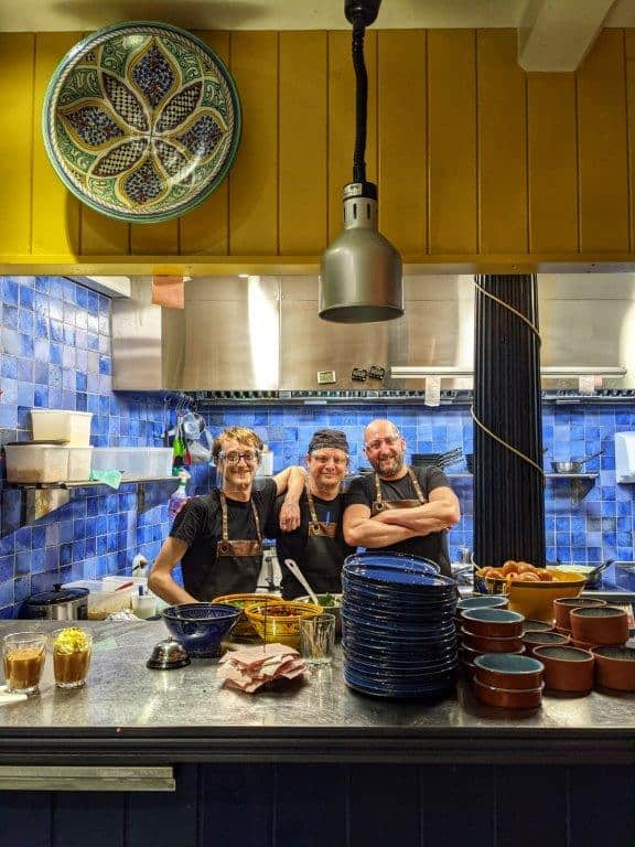 Three chefs standing behind the pass in a restaurant kitchen smiling to camera wearing visors