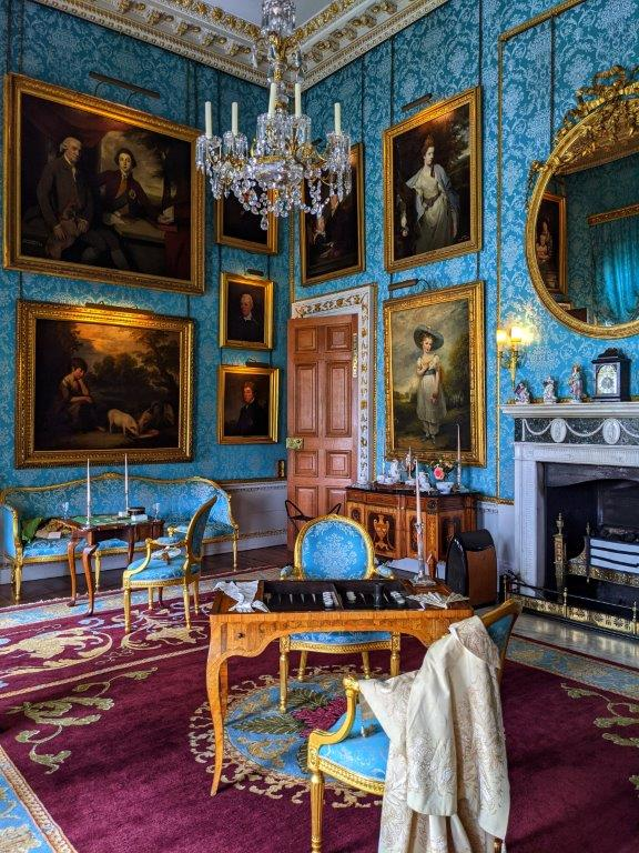 A grand room ornately decorated, with antique furniture and turquoise wallpaper and classic paintings hung on the walls