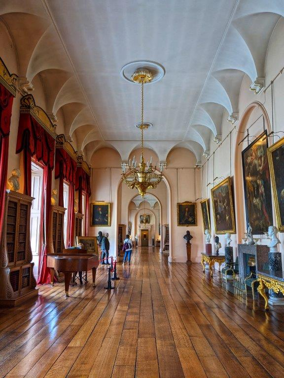 A grand hall with floor to ceiling windows, draped red velvet curtains, a chandelier and classic portraits hung on the walls