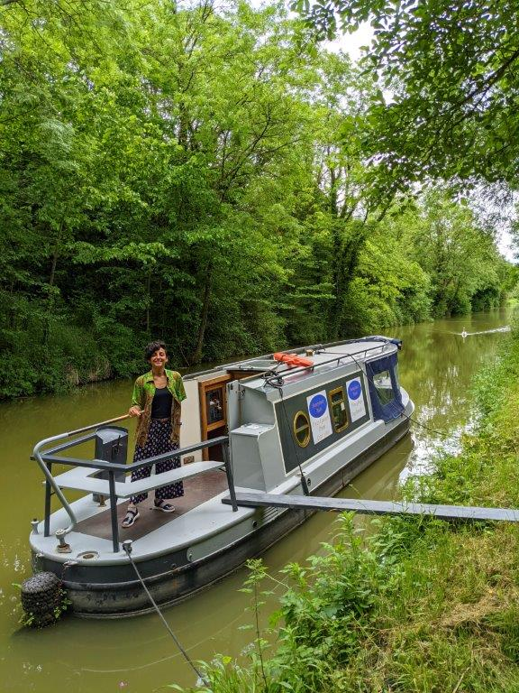 A narrowboat moored up on a canal with a wooden plank linking it to the bank and a woman standing on deck