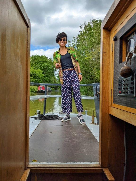 A woman in green shirt and sunglasses and a big smile steering the tiller of a narrowboat