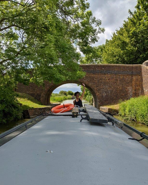 A view down the length of the roof of a narrowboat passing under the arch of a bridge, with a woman at the far end steering and waving to the camera