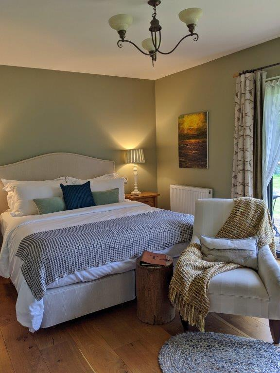 An elegant bedroom with a generous double bed, comfy armchair and soft furnishings