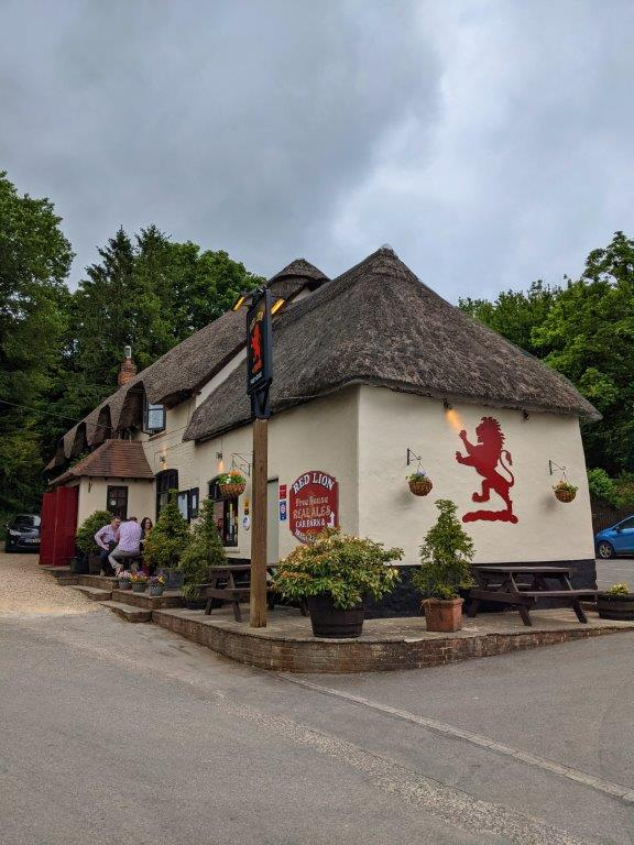 A pub with a thatched roof and a large red lion emblem on the side of the building
