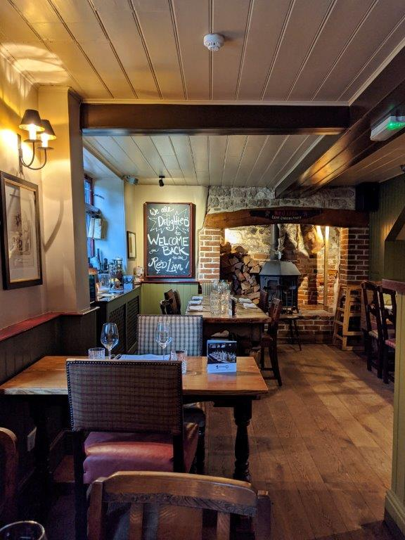 The cosy interiors of a pub with wooden floor, wood panelled ceiling and a large hearth at the back of the room
