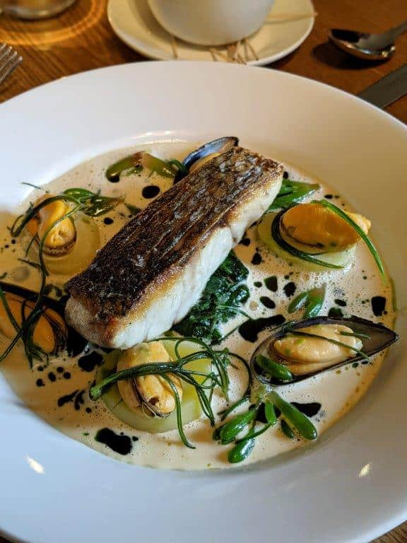 A beautiful dish of pan-fried stonebass on a bed of confit potatoes and mussels set in a shallow white bowl
