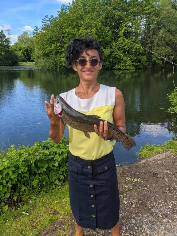 A woman in a sleeveless white and yellow top, sunglasses and a long navy skirt proudly holding up a trout she caught