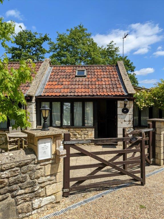 A stone cottage with terracotta tiled roof and a gated entrance