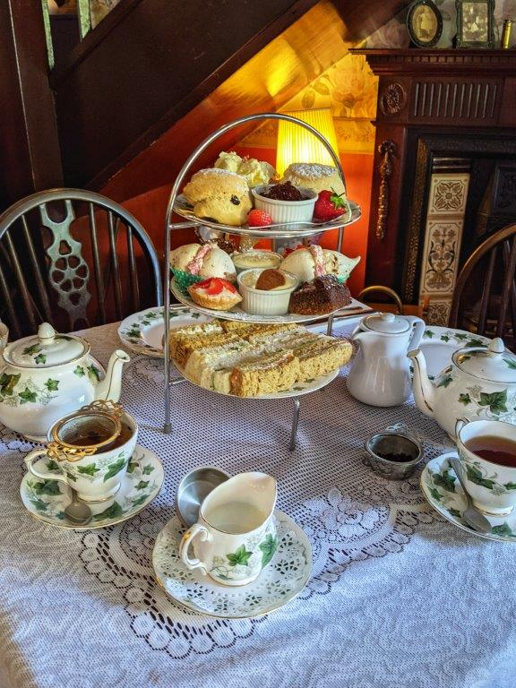 A traditional afternoon tea spread with three tiers of finger sandwiches, cakes and scones, on a lace tablecloth with a bone china tea set