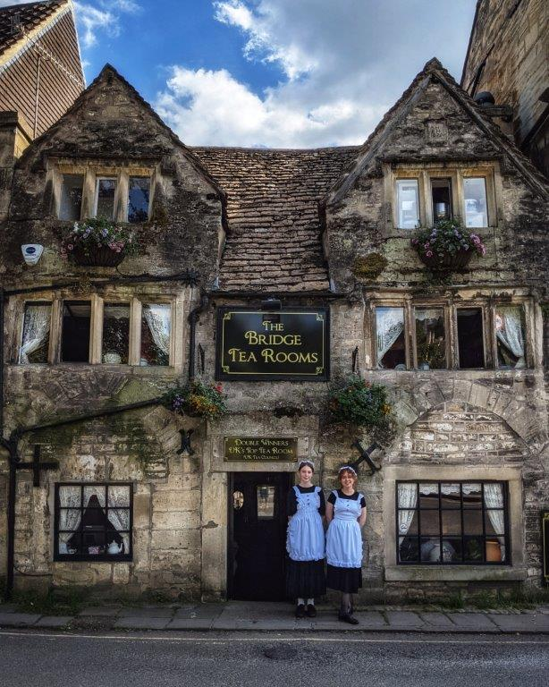 A medieval looking three storey stone buildings with 'The Bridge Tea Rooms' above the entrance, two young women in tea maid outfits standing out the front