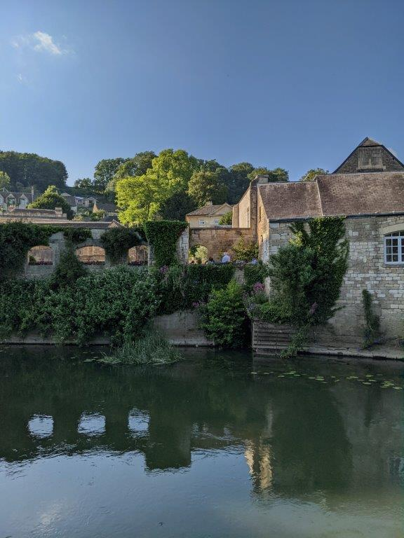 View across the width of a peaceful river, old stone buildings and lots of climbing vegetation on the opposite bank
