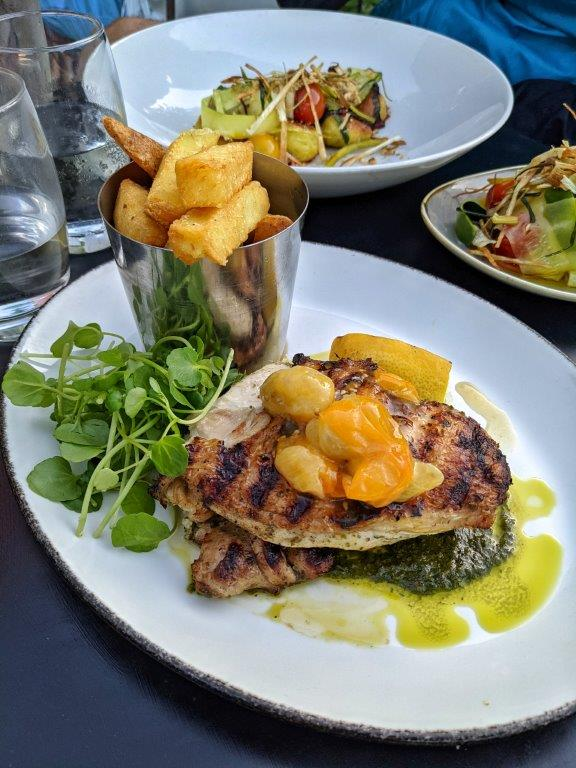 A plate of charred chicken with confit yellow tomatoes on a green sauce with a pile of chunky chips