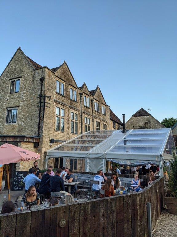 The outdoor seating area of a restaurant with patrons enjoying themselves eating and drinking under a blue sky
