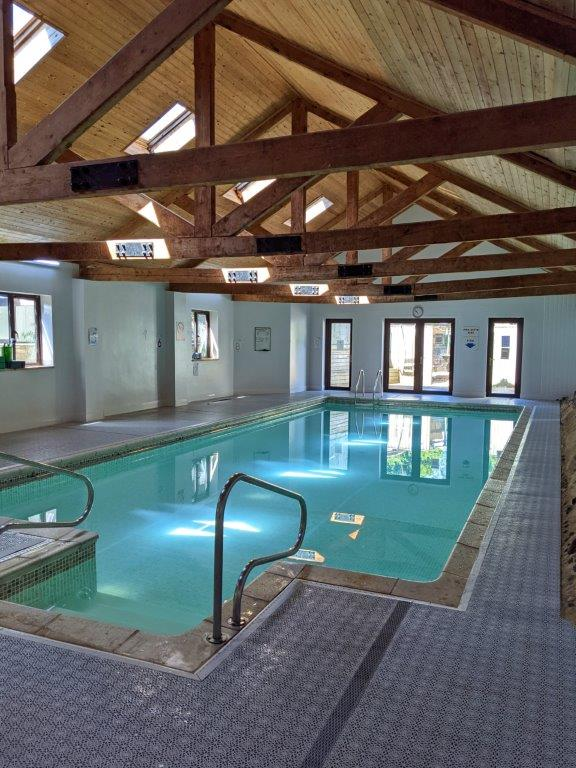 An indoor swimming pool set inside a converted barn with exposed wooden beams
