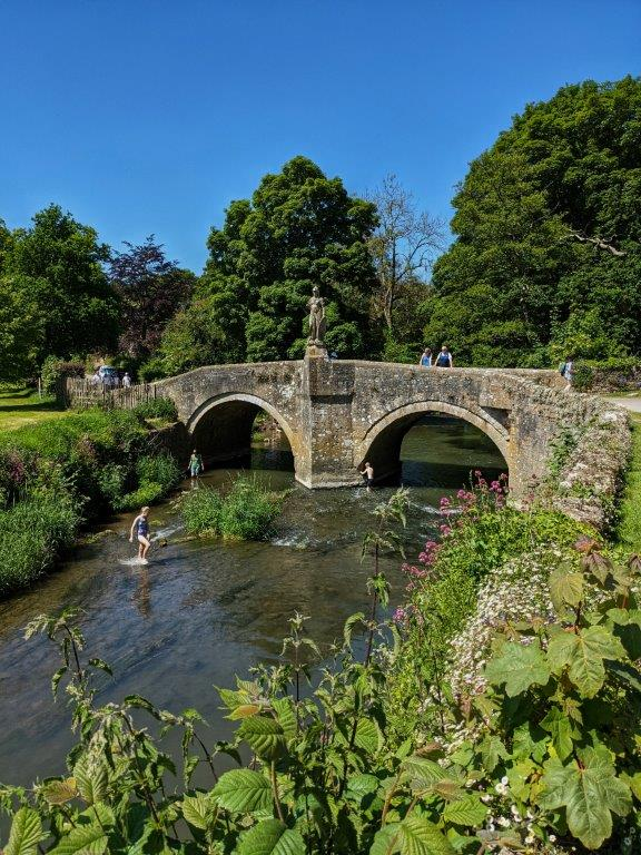 A river on a sunny day with children splashing in the shallows, an old stone bridge with two arches passing over it