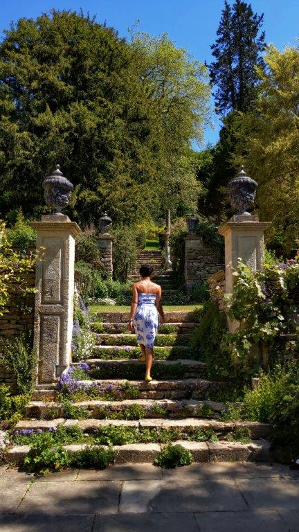 A woman in a white and blue strapless dress walking up stone steps under the sunshine in a lush Italian garden setting