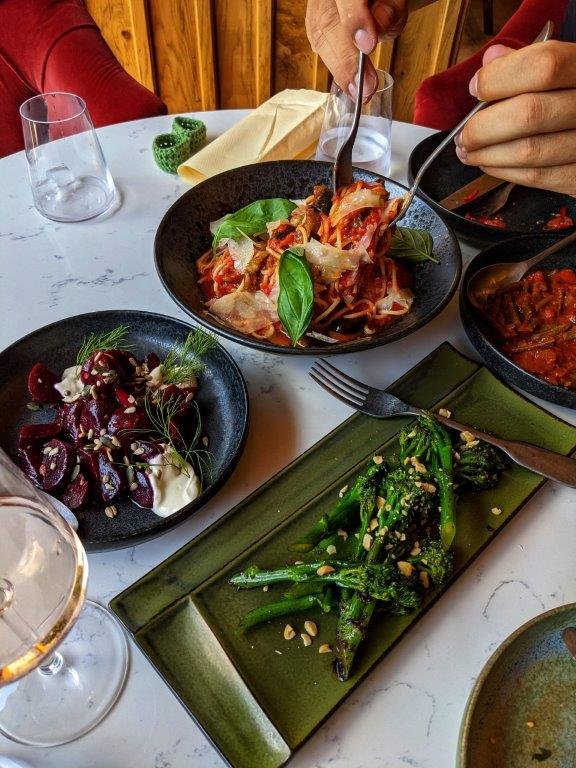 An assortment of dishes laid out on a white marble table with two hands forking up a big bowl of pasta in the middle