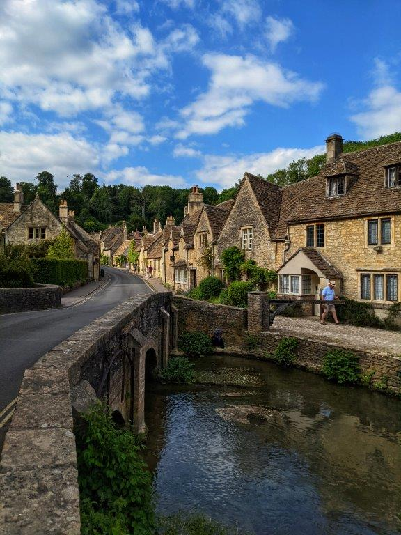 A picturesque English village road lined with old and beautiful listed houses, running over a river