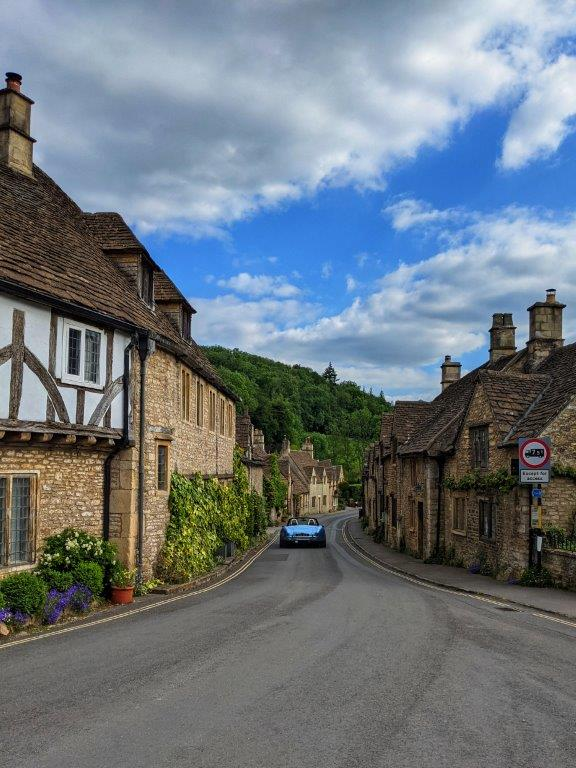 View down an English village road lined with beautiful old houses, with an electric blue sports car zooming off into the distance