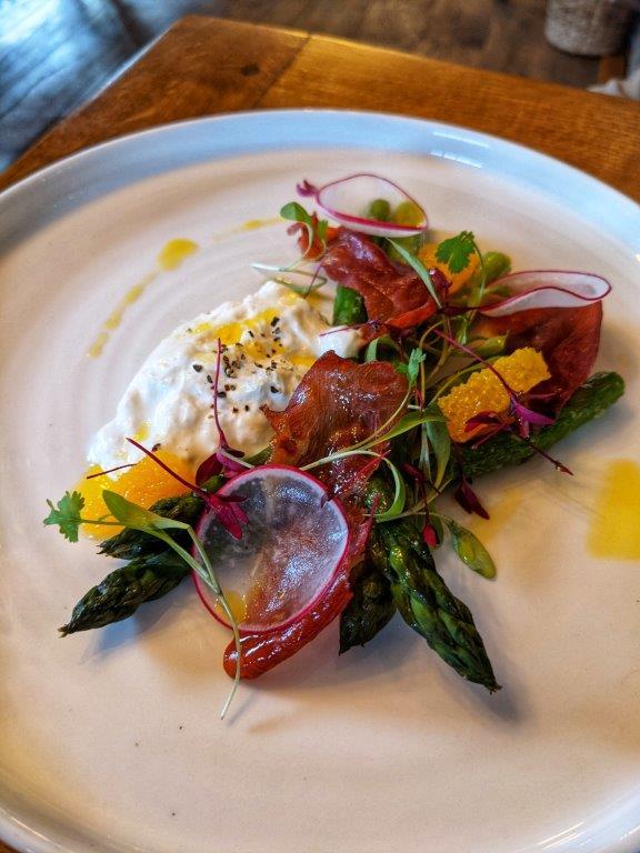 A beautifully plated dish of asparagus, burrata, crispy pancetta and orange segments