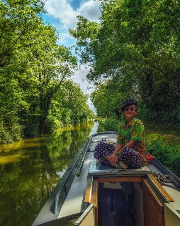 A girl in a green short sitting crossed legged on the roof of a narrowboat moored on a peaceful canal surrounded by lush green trees
