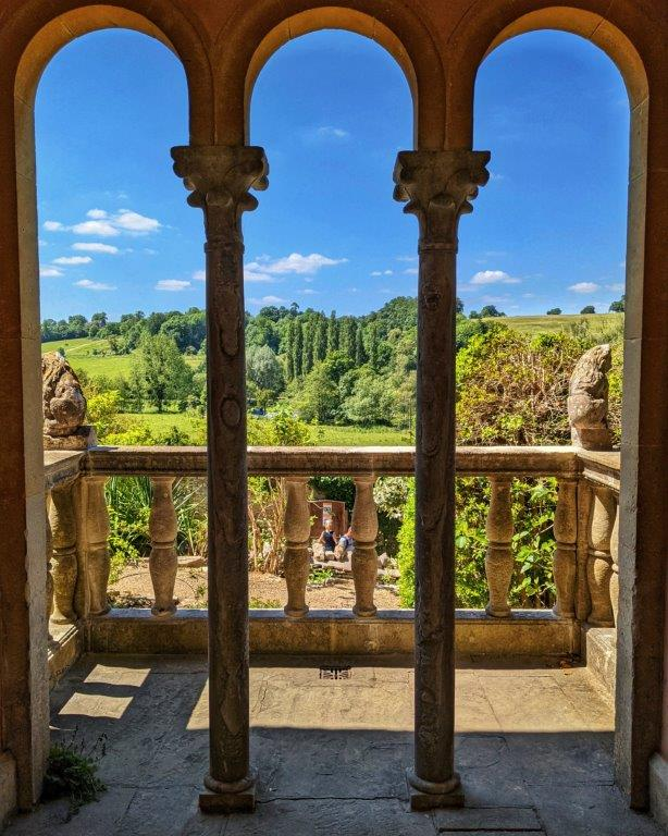 A view through three adjoining narrow archways onto a balcony and then over a lush green garden and blue skies beyond