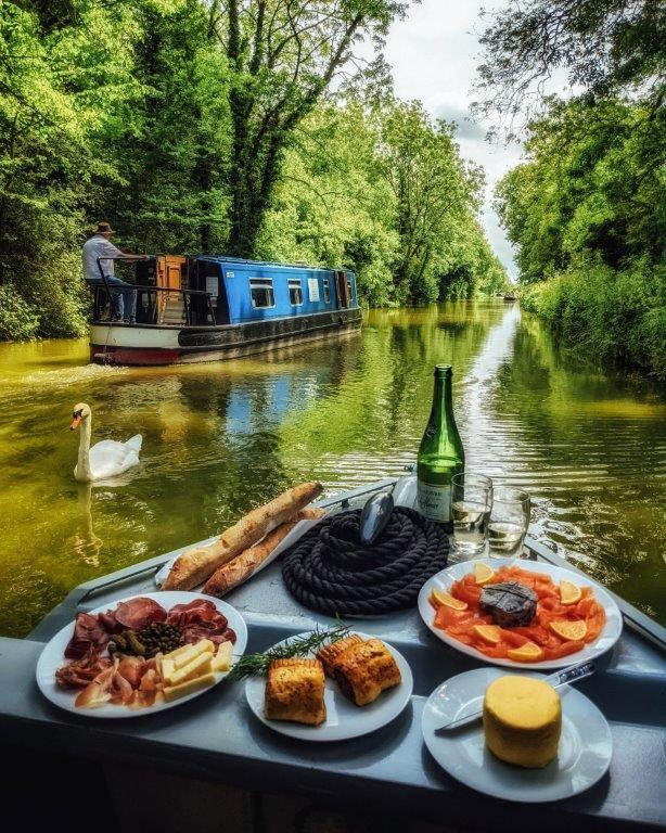 A delicious array of picnic hamper edibles arranged at the front of a narrow boat against a backdrop of a peaceful canal with a swan and passing narrowboat